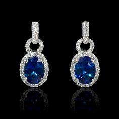 These gorgeous 18k white gold dangle earrings, designed in Italy, contain 2 blue sapphires, weighing 2.78 carats with 76 round brilliant cut white diamonds of F color, VS2 clarity and excellent cut and brilliance, weighing .60 carat total.