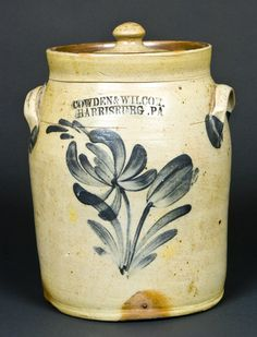 "Price Realized: $ 460.00 One-Gallon Cobalt-Decorated Stoneware Jar with Lid, Stamped ""COWDEN & WILCOX / HARRISBURG, PA,"" circa 1865, cylindrical jar with rounded shoulder and applied lug handles, decorated with a brushed cobalt flowering plant with spitting tulip and bud. Includes original salt-glazed stoneware lid. 2"" vertical hairline above one handle. Faint 2 1/2"" line on underside, extending 4"" up reverse side of jar. Lid in mint condition. H (including"