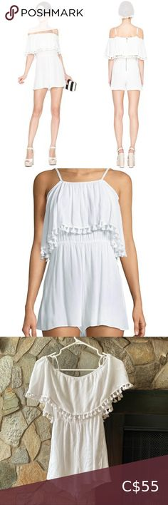 Alice + Olivia Dory White Off Shoulder Pom Pom In excellent condition. This romper features an off shoulder neckline, delicate and adjustable shoulder straps, ruffle and pom detailing, and a zip closure at back. Perfect for hot summer days or nights. Alice + Olivia Pants & Jumpsuits Jumpsuits & Rompers