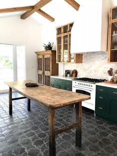 Love this reclaimed wood kitchen island table. Green kitchen cabinets, wood beam ceiling, and gray tile kitchen floor. Wood Kitchen Island, Green Kitchen Cabinets, New Kitchen, Dark Cabinets, Awesome Kitchen, Kitchen Islands, Kitchen Backsplash, Kitchen With Tile Floor, Vintage Kitchen
