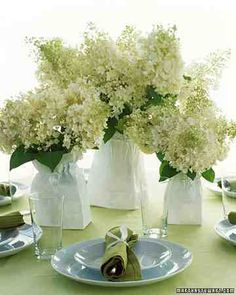 Vases of varying sizes, shapes, and materials can be unified with mere paper bags to serve as fresh, bright centerpieces at a casual party. Slip the plain white lunch bags over the containers and cinch the tops loosely with ribbons tied in bows.