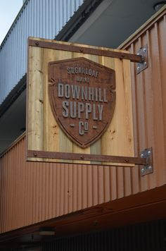 A custom-made sign for Downhill Supply Co. at Sugarloaf - an eclectic mixture of spruce, fir and rusted metal work by Maine Heritage Timber. Retail Signage, Wayfinding Signage, Signage Design, Carved Wood Signs, Metal Signs, Wooden Signs, Industrial Signage, Blade Sign, Neon Box