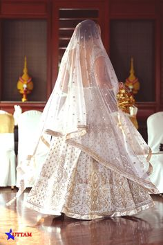 Bridal Lehengas - White Wedding Lehenga | WedMeGood |Twirling Bride in a White Wedding Lehenga with Golden Embroidery, Backless Blose and White Net Dupatta #wedmegood #indianwedding #indianbride #white #lehenga #bridal #gold #twirl
