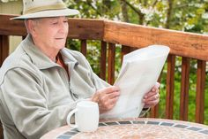 Active Healthy Elderly Man Reading Newspaper and Drinking Coffee Outside at a Table on Deck