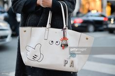 A guest poses with an Anya Hindmarch stickers bag on Day 2 of Paris Fashion Week Womenswear FW 15 on March 4, 2015 in Paris, France.