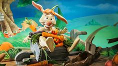 Rabbit sits in a wheelbarrow with carrots and tomatoes in his lap