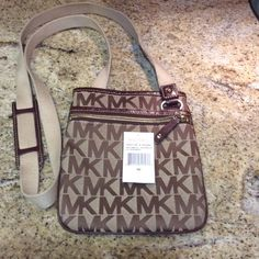 Micheal Kors cross body leather trim. AUTHENTIC Micheal Kors cross body brown leather trim. strap is adjustable and is clean of any dirt or signs or wear- like NEW Michael Kors Bags Crossbody Bags