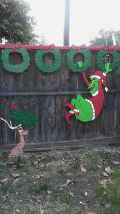 Handmade Christmas Grinch swinging fron LIGHT UP wreaths and Max with LIGHT UP wreath on antlers yard art