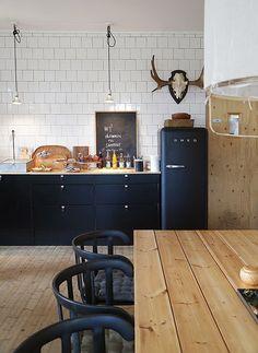 Keuken met de mat zwarte SMEG koelkast. Goede verdeling van design items (witte hanglamp Ay Illuminate) en zwarte composiet eetkamerstoelen van IKEA.