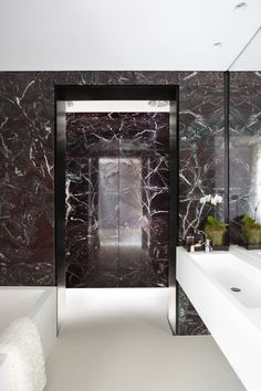 Black and white bathroom with black marble. The Tusculum Residence by Smart Design Studio. Nice and luxurious.