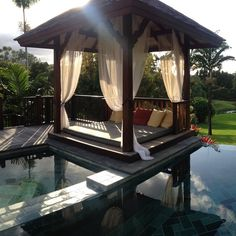 A Bali bed is an outdoor daybed built on a platform usually set near a pool. Framed by four wooden posts, they are strung with curtains for the added option of privacy. Coastal resorts throughout the world may offer a Bali bed on the beach, where you can sunbathe during the day and sleep under the stars at night.