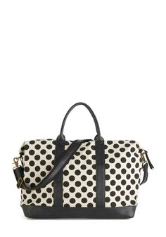 Travel Bug Weekend Bag. A bad case of wanderlust is even more fun carrying this ivory canvas weekend bag with black polka dots!  #modcloth