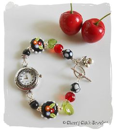 Charmed Cherry Beaded Watch...A fun little bracelet watch designed with tri-colored poppy flower glass lampwork beads, white polka dotted glass lampwork beads, Czech pressed glass leaves, and other assorted glass beads. The extra cuteness is the Cherry charm that hangs from the easy on easy off toggle clasp. The watch is 7 3/4 inches in length. $45 #CherryWatch #CherryChick #Lampwork #BeadedWatch