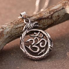"""Om - eternal and mystical syllable that symbolizes the entire universe. Circle Om pendant wrapped in a serpent. Handcrafted in Thailand .925 Sterling Silver. -Sterling Silver .925 -Handmade in Thailand -Pendant 1.25""""H x 1""""W-.925 Silver Chain 16""""-Item #SIP19"""