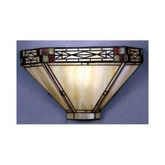 This mission style lamp has beige glass shade with metal filigree along the edge and corner accents of red and green glass.