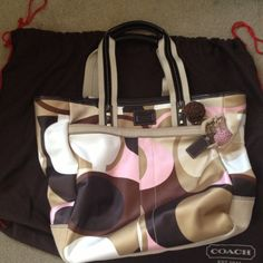 Coach Tote in Brown/Khaki/Pink Gently used (twice) Coach tote. Some notable wear on bottom areas of bag which I have photographed. I have not tried to clean the small stain out, so it may be cleaned off. Cute pink lining inside with zipper pocket and pocket for cellphone. There is also a zippered outside side pocket. I have added approximate measurements that I took. Let me know if you have any questions. Coach Bags Totes
