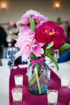mason jar centerpiece. Use silver ribbon to tie a bow around the jar. get light pink flowers or white and dye pink. Put glitter in the water. Table number between ribbon and glass