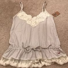 GorgeousNWT Hollister floral cami light grey Gorgeous floral applique neckline Hollister camisole in light grey. Brand new with tag, size small. Front tie and lace hem detail. Super cute with skinny jeans and a light cardigan. No PayPal or trades. Hollister Tops Tank Tops