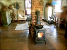 Wood-Burning Stove & Chimney in the Middle of a Room With a Wooden Floor