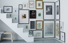 different sizes of framed pictures hanging in a corner and above stairs