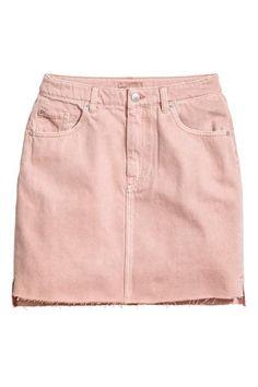 12ee32f97f786 Een korte 5-pocketrok van gewassen denim met een onafgewerkte rand  onderaan. De rok heeft een gulp met rits en knoop