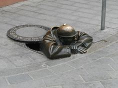 """The most famous statue in Bratislava Slovakia is probably a bronze statue entitled """"Cumil"""". The statue is of a man peeking out from under a manhole cover."""