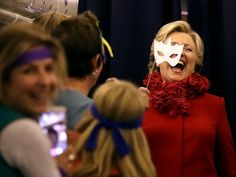 Hillary Clinton holds a mask as she jokes with members