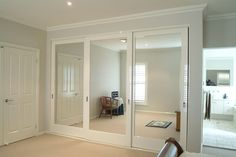 wardrobe sliding door system as room divider...like the idea of mirrors for a larger space