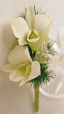 A simple, yet clean and elegant, boutonniere made of two white dendrodium orchids and ming fern.