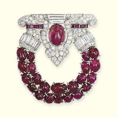 AN ART DECO RUBY AND DIAMOND BROOCH The half circle of cabochon rubies to the pavé-set and baguette-cut diamond openwork surmount with central cabochon ruby, circa 1925, 4.5 cm long, with French assay mark for platinum