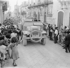 THE BRITISH ARMY IN SICILY 1943. Quad artillery tractors and 25pdrs of 51st Highland Division are cheered by crowds as they enter Militello, 15 July 1943.
