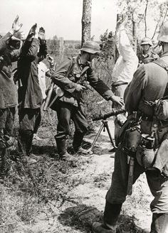 Caught in the act, what appears to be partisans or straggling soldiers masquerading as civilians are being searched by German soldiers. The man in the foreground is armed with an MG 34 machine gun and display his equipment, the shelter quarter, the M31 canteen, his entrenching tool carrier, to which is also attached his bayonet. The man in the background has a Luger P08 and a single-barrel spare barrel carrier slung on his back as well his gas mask canister. Photo from 1941.
