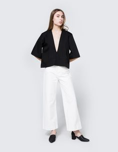 Modern blouse from Toit Volant. Available in White, Black, Camel, Khaki or Caribbean. Plunging V-neckline. Slightly dropped shoulders. Half bell sleeves. Horizontal dart at center waist. Straight hem. Tonal topstitching. Casual fit. • Poplin • 35% co