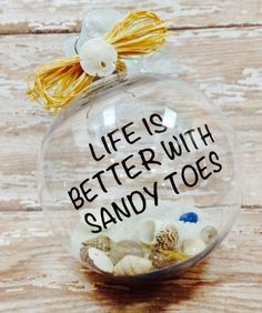 This acrylic ornament is 3.5 inches round, lettered in high quality brown vinyl with the phrase, Life is better with sandy toes, and filled with sand, shells, sea glass, starfish and sand dollars. Topped off with a raffia bow. All of our ornaments are customizable. Different wording, additional wording or wording color changes are available.