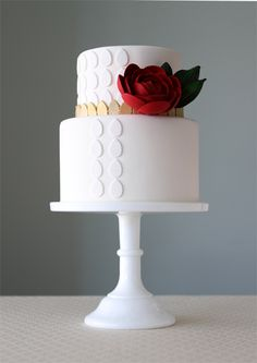 Simple white two tier cake with white and gold gumpaste leaves. A red rose sits alongside the top tier.