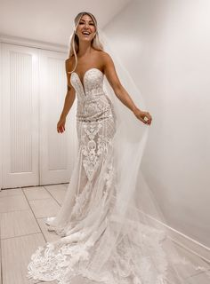 This curve-hugging, layered lace wedding dress is beautifully detailed with a plunging sweetheart neckline, flattering princess seams, and all over intricate beadwork and sequins. Complete with a beautiful scalloped chapel train. | #beadedweddingdress #modernweddingdress | Style CWG878 | Shop this dress and more at davidsbridal.com | Photo by: @amandalynrose