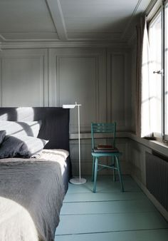 Kinfolk Book II home, shades of grey and green, wall panels, wooden floors - the FLOS Tab F floor lamp complements this minimalist, contemporary bedroom.