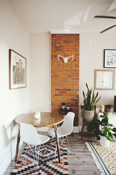 Dining Room decor ideas - small dining room in eclectic bohemian style with little round table, Eames inspired white chairs, zig zag rug and brick feature wall | Urban Outfitters - Blog - About A Space: Ally Couch's Toronto Small Space