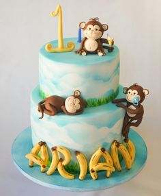 A birthday cake requested to have monkeys and bananas and blue and white colours.
