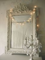 fairy lights draped over an ornate mirror