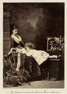 Czarina Maria Feodorovna, mais tarde Imperatriz da Rússia, e grão-duque Nicolau Alexandrovich, mais tarde, Nicolau II. Czarina Maria Feodorovna está sentada em um muro baixo, olhando para o Grão-Duque Nicholas Alexandrovich que está deitado na parede ao seu lado, olhando para um livro que está descansando em seu colo. À esquerda há um pilar e à direita uma treliça coberta de hera. Cerca de 1872.