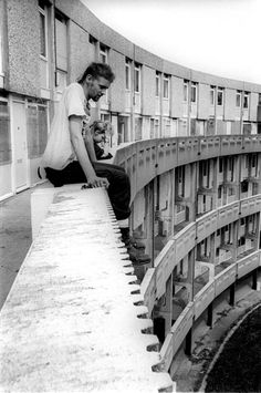Image by Ian Robinson. Taken of The Crescents, Hulme, Manchester. 19th century slums were cleared out to create this giant housing estate, but design problems caused them to become unpopular, and they were made adults-only because of the dangerous balconies. Apparently taken over by countercultural types in the 80s and even used for club nights. More, fascinating info on Wikipedia.