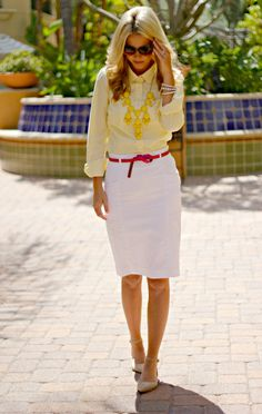 Light yellow blouse, white pencil skirt with pink belt, nude flats, and yellow bubble necklace.