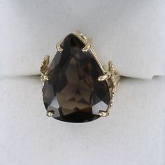 10KT SMOKY TOPAZ RING A SMOLDERING SMOKY TOPAZ IS THE CENTERPIECE OF THIS INTRIGUING RING. THE TOPAZ IS PEAR-SHAPED AND SET IN AN 10KT YELLOW GOLD OPENWORK MOUNTING DECORATED WITH FLOWERS AND LEAVES ON EITHER SIDE. THIS RING PROVIDES A RICH, SUBSTANTIAL LOOK.$495