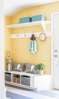 Yellow and blue mudroom features walls painted bright yellow lined with a shelf lined with blue bins and a row of hooks over a built-in bench filled with galvanized steel bins and gray pillows alongside a gray striped floor.