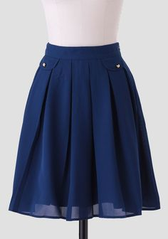 A Ruchette must-have, this smooth-as-silk dark blue skirt is adorned with faux front pockets and a banded waist for a defined silhouette. Perfected with pleats for added flare and a hidden side z...