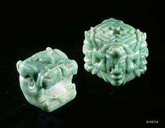 Description: Maya. jade. Square beads. one in the form of a jaguar's head. One carved with portraits. 6 cm. per side.