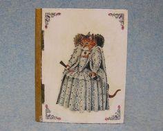 ★古い本(ブック)を象った木製のジュエリーボックスです。ヴィクトリア朝の猫の世界がユニークでユーモラスな作品で、扉(表紙)は女王の猫が立体的な装飾とともにゴージャスな雰囲気をかもし出しています。扉を開くと王宮での秘めた愛、それを目撃するメイドなど、いろい...