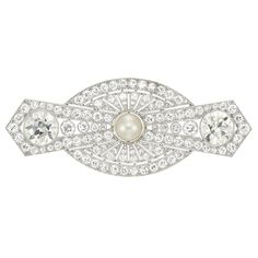Platinum, Button Pearl and Diamond Brooch  The pierced stylized bow motif centering one pearl approximately 8.0 mm., tipped by 2 old European-cut diamonds approximately 7.00 cts., set throughout with 90 old European-cut diamonds approximately 5.80 cts., accented by single-cut diamonds, circa 1925