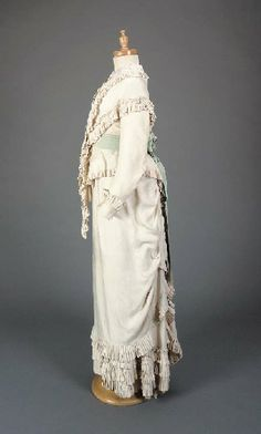 A young girl's dress, of cream silk, comprising bodice and pelerine with frilled trim, skirt fitted in front with a draped apron, with a pale blue silk sash stamped Mrs Mason Modes & Robes ?, 1870s with later lace collar, on a child's mannequin, Christie's. This dress was worn by Annie Holden in a painting dated 1877 by Samuel Sidley which was exhibited at the Royal Academy in the same year. The painting featured Annie, the daughter of Angus Holden, and her brother Ernest seated on a pony.